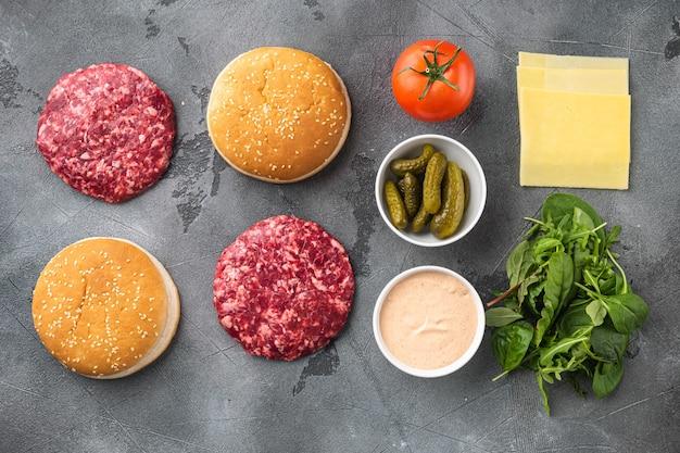 Hambúrguer caseiro. rissóis de carne crua, pãezinhos de gergelim com outros ingredientes definidos, em fundo de pedra cinza, vista de cima plana lay