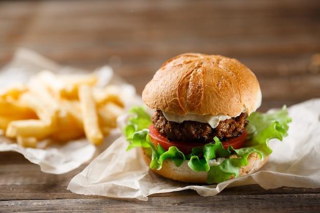 Hambúrguer caseiro saboroso e batatas fritas na mesa de madeira