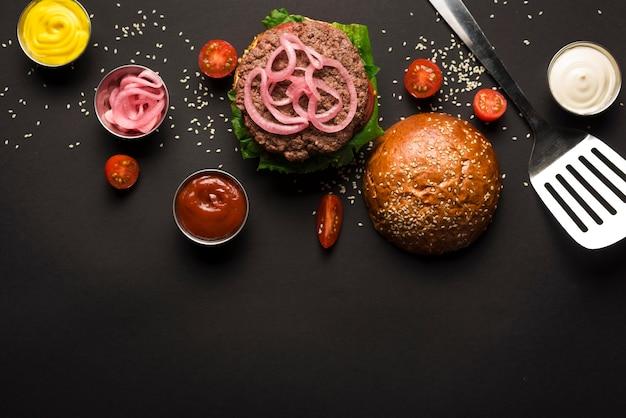 Hambúrguer clássico com vista superior, rodeado de molhos