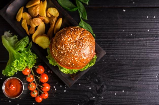 Hambúrguer clássico de alto ângulo com batatas fritas e tomate cereja