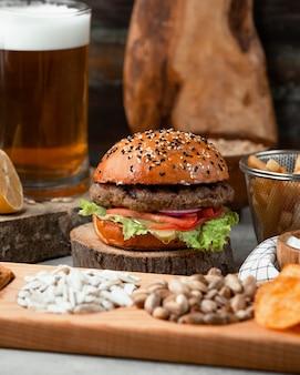 Hambúrguer clássico servido com batatas fritas e cerveja