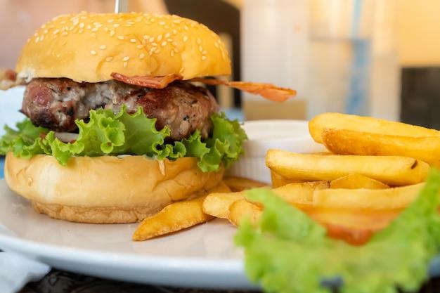 Hambúrguer com bacon servido em um prato branco com batata frita e alface.