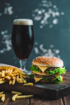 Hambúrguer com batatas e cerveja escura em uma placa de madeira sobre um fundo azul-acinzentado