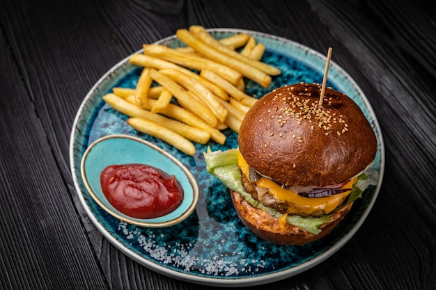 Hambúrguer com batatas fritas e molho em uma mesa de madeira escura