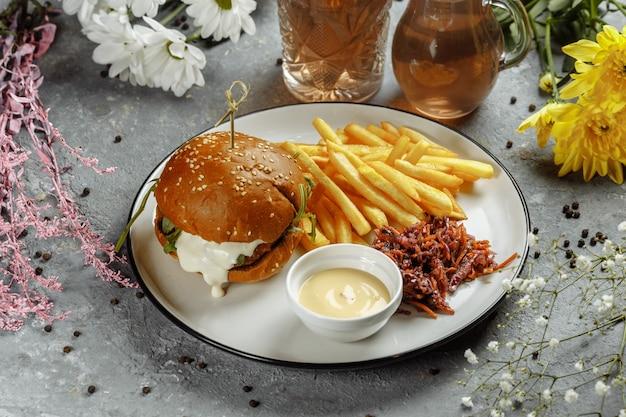 Hambúrguer com batatas fritas e molho num prato branco.