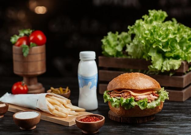 Hambúrguer com batatas fritas em uma mesa de cozinha de madeira