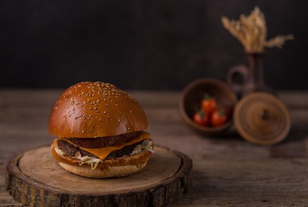 Hambúrguer com batatas fritas, ketchup, mostarda e legumes frescos em uma placa de corte de madeira.