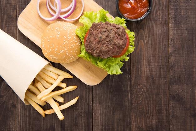 Hambúrguer com batatas fritas no fundo de madeira