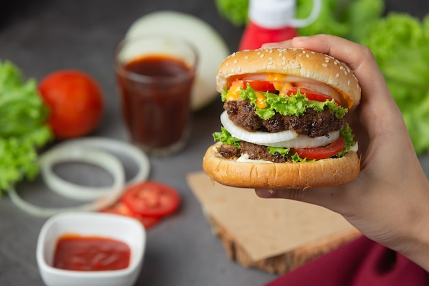 Hambúrguer com carne frita, tomate, picles, alface e queijo.
