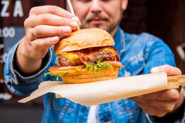 Hambúrguer com carne, legumes, creme de queijo e molho closeup nas mãos de um homem.