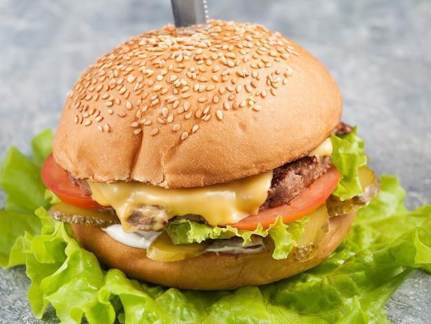 Hambúrguer com carne, picles, tomate e queijo. fechar-se