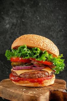 Hambúrguer com carne, queijo e legumes em fundo escuro. cozinha americana. comida rápida