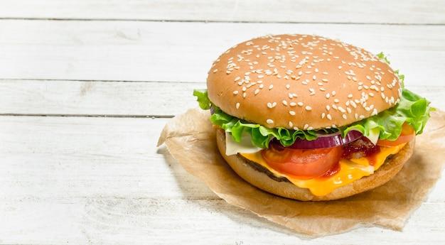 Hambúrguer com carne, queijo e vegetais no papel em um fundo branco de madeira
