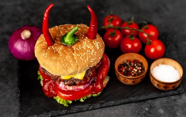 Hambúrguer com chifres de pimenta vermelha na pedra