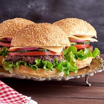 Hambúrguer com costeleta frita, queijo e legumes em um pão redondo de farinha de trigo