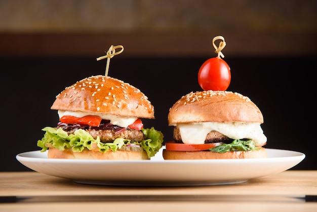 Hambúrguer com costeleta, molho, tomate, alface e gergelim na chapa branca em fundo escuro