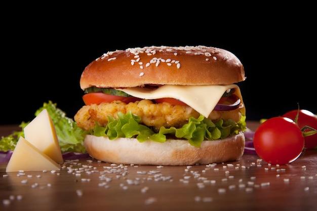 Hamburguer com galinha e queijo, alface, pepinos, tomates e cebolas em um fundo preto.