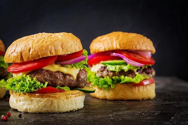 Hambúrguer com hambúrguer de carne de bovino e legumes frescos na superfície escura.