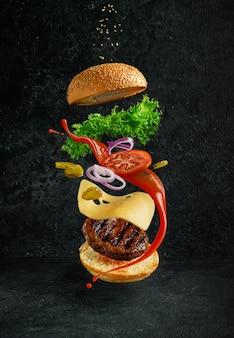 Hambúrguer com ingredientes flutuantes em fundo escuro