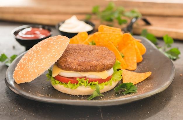Hambúrguer com molho de tomate e maionese, acompanhado de nachos