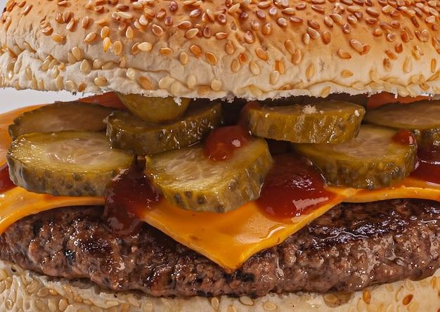Hambúrguer com pão de gergelim, queijo cheddar derretido, picles e maionese, ketchup no fundo branco.