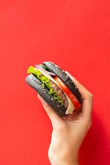 Hamburguer com pão preto sobre fundo vermelho