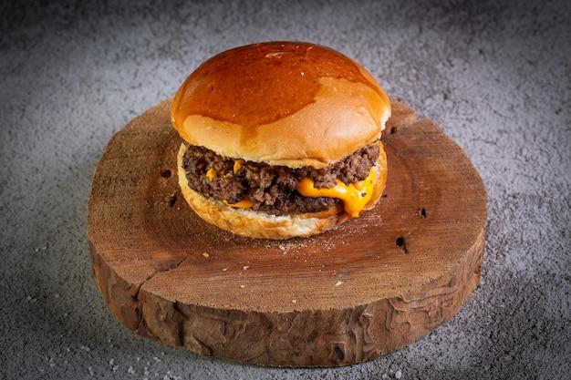 Hambúrguer com queijo cheddar em prato de madeira
