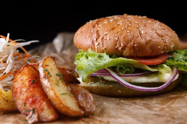 Hambúrguer com queijo, legumes e batatas