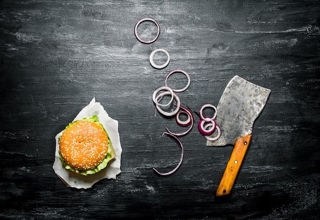 Hambúrguer com rodelas de cebola e uma velha machadinha. em um quadro negro. vista do topo.