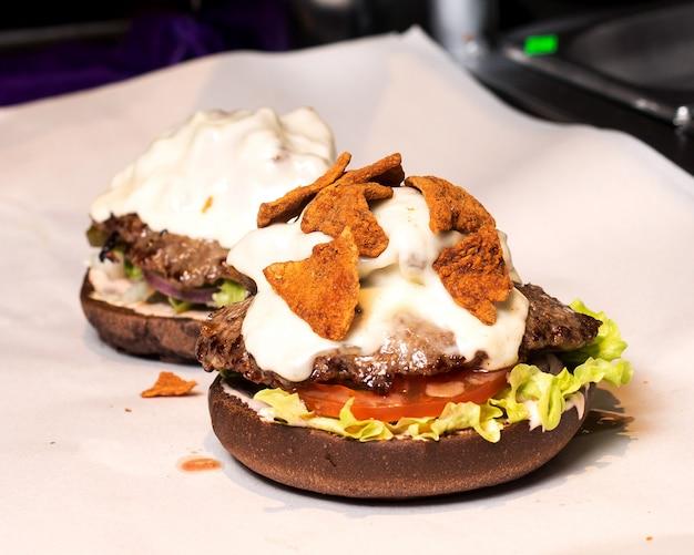 Hambúrguer com tomate alface, costeleta de carne e queijo derretido