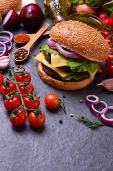 Hambúrguer com tomate e mais comida na superfície preta