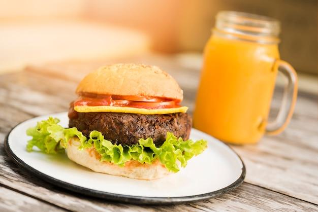 Hamburguer com tomates; queijo e alface servido com copo de suco na mesa de madeira
