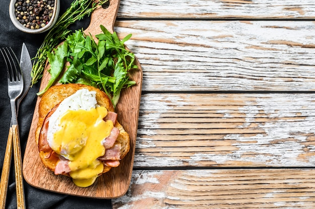 Hambúrguer de café da manhã com bacon, ovo benedict, molho holandês em pão de brioche. enfeite com salada de rúcula. fundo branco.