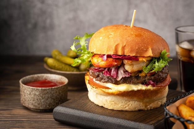 Hambúrguer de camarão e carne, copo de bebida, fatias de batata frita, pepino e sause. close-up, luz de fundo.