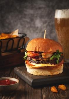 Hambúrguer de camarão e carne, copo de cerveja, fatias de batata frita e sause. close-up, copie o espaço.