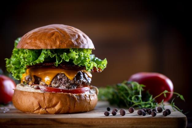 Hambúrguer de carne artesanal com cheddar, bacon, alface e molho em fundo de madeira