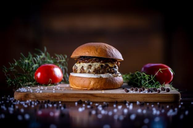 Hambúrguer de carne artesanal com queijo, cebola caramelizada e molho em fundo de madeira