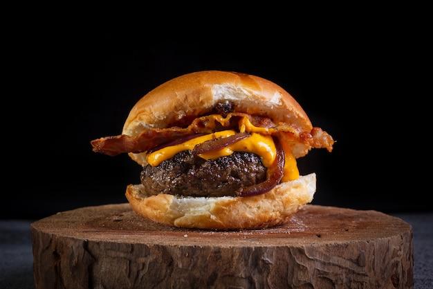 Hambúrguer de carne artesanal com queijo cheddar, bacon, cebola caramelizada e molho de mostarda com alho