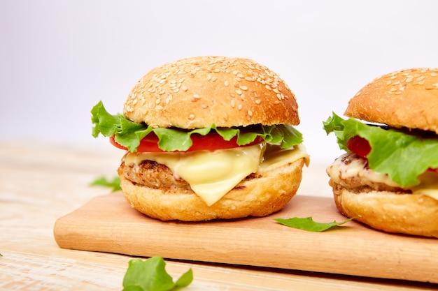 Hambúrguer de carne artesanal na mesa de madeira sobre fundo claro