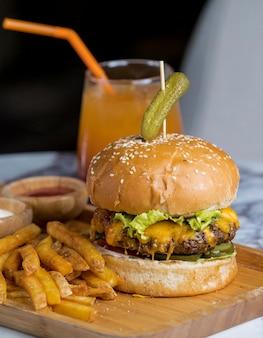 Hambúrguer de carne coberto com cornichon, servido com batatas fritas