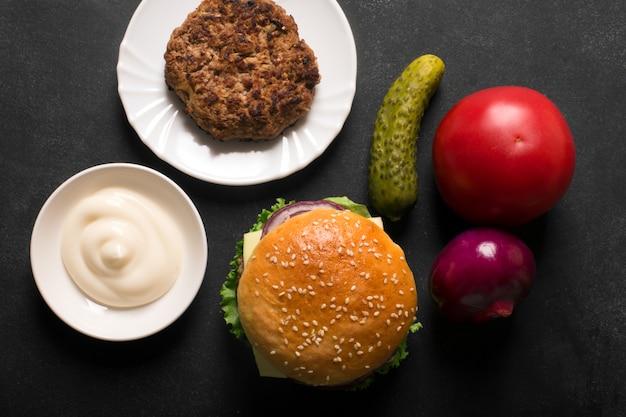 Hambúrguer de carne com alface e molho no quadro preto
