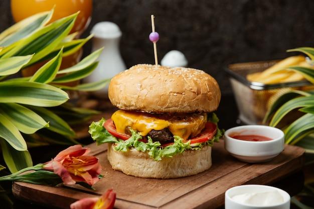 Hambúrguer de carne com alface, queijo cheddar derretido, tomate, maionese e ketchup