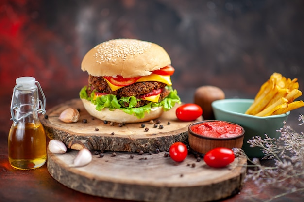 Hambúrguer de carne com batata frita no fundo escuro de vista frontal