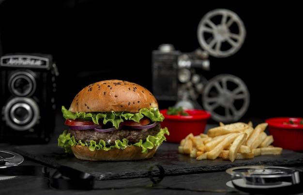 Hambúrguer de carne com cebola picada e tomate dentro de pão e com batatas fritas em uma bandeja de pedra