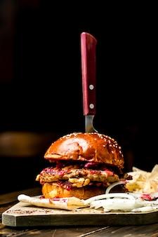 Hambúrguer de carne com faca na vista lateral superior