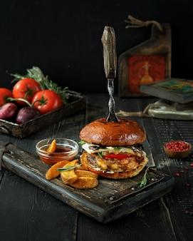 Hambúrguer de carne com fatias de batatas assadas e molho de tomate na placa de madeira vintage