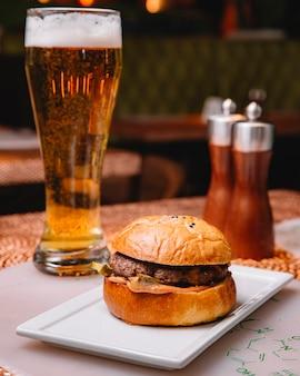 Hambúrguer de carne com molho de pepino em conserva, servido no restaurante com cerveja vertical