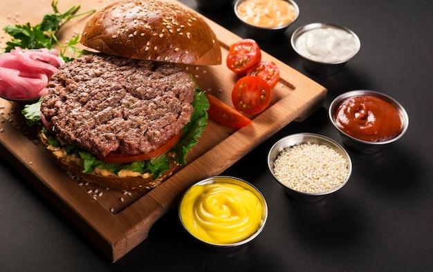 Hambúrguer de carne com molhos prontos para serem servidos