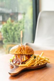 Hambúrguer de carne com queijo e molho em prato de madeira