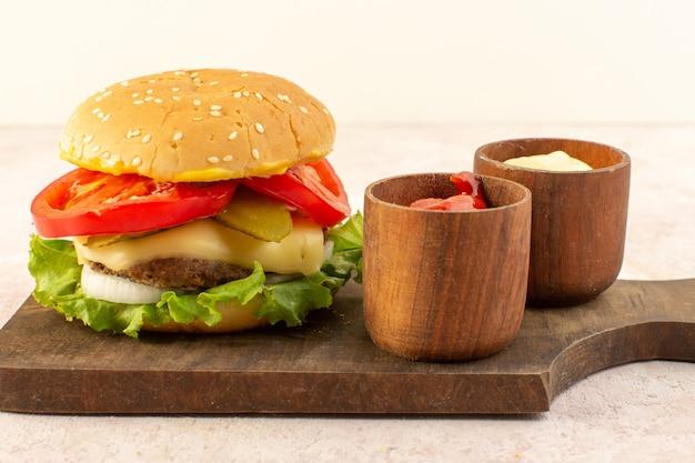 Hambúrguer de carne com queijo e salada verde junto com ketchup e mostarda em mesa de madeira